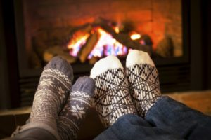 Feet warming by fireplace in a winter getaway package